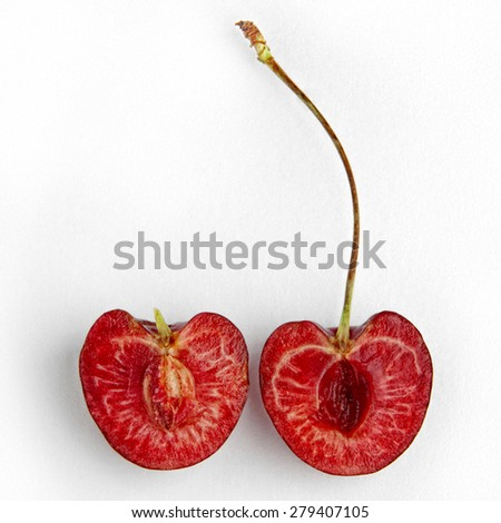 Two pieces of cut cherry isolated on white background. Half of ripe, juicy and delicious cherry. - stock photo