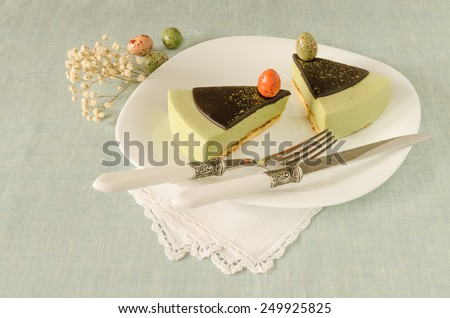 Two pieces of easter cake with tea matcha decorated chocolate ganache and sweet-stuff eggs on white plate.  - stock photo