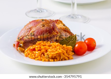 Two pieces of eisbein on a plate with rice and cherry tomatoes - stock photo