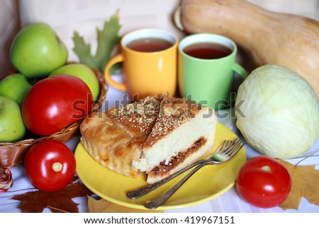 Two pieces of fresh baked cabbage pie (tart, cake, calzone, kulebyaka) on the yellow plate serving with red tomatoes, green apples, pumpkin, two cups of tea, foliage and vintage forks, selective focus - stock photo