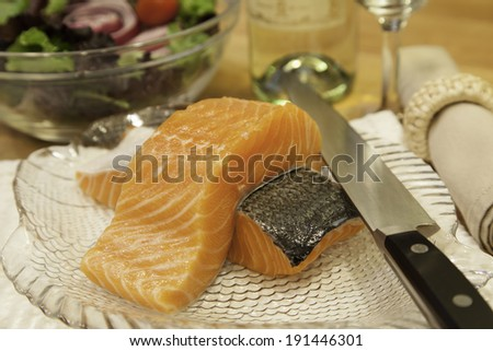 Two pieces of fresh salmon sit atop a plate ready to be cooked.  A sharp knife rests on the side of the plate.   - stock photo
