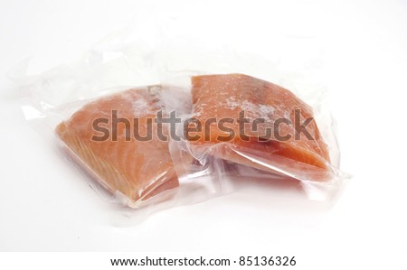 two pieces of frozen salmon on white background - stock photo