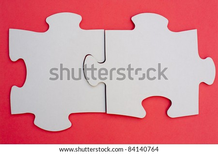 Two pieces of jigsaw puzzle on red cloth - stock photo