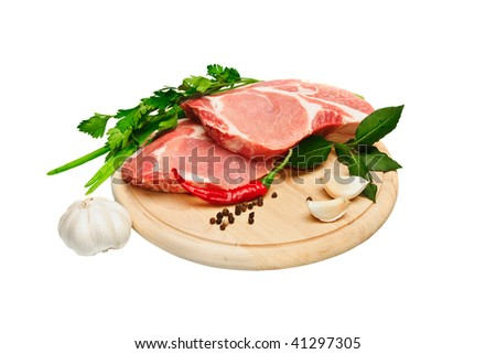 Two pieces of meat and spice on a wooden board - stock photo