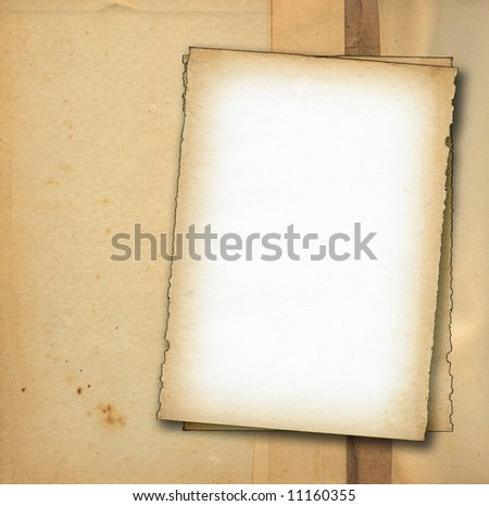 two pieces of old paper against stained dirty background, edges are very frayed - stock photo