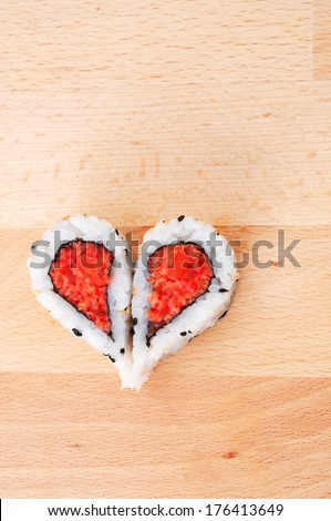 Two pieces of sushi forming the heart shape on wooden cutting board - stock photo