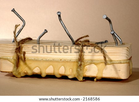 two pieces of wood joined with glue, nails and twine - stock photo