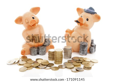Two piggy bank and piles of coins over white background - stock photo