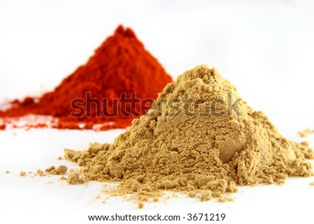 two piles: ground ginger on white background with red paprika pile, bright colors. - stock photo