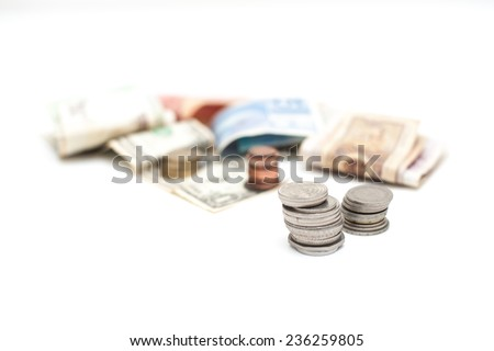Two piles of coins with out of focus money in background