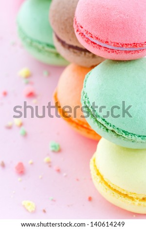 Two piles of colorful macaroons on pastel pink background with small crumbs - stock photo