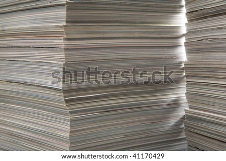 Two piles of thick old magazines, in beautiful illumination. - stock photo