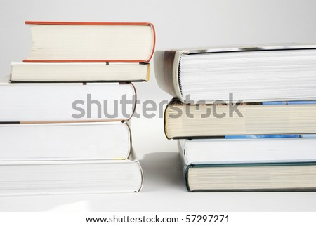 Two piles of various color of hardcover books - stock photo