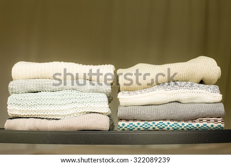 Two piles of warm sweaters for fall or winter on a shelf in a closet. Soft draped background. - stock photo
