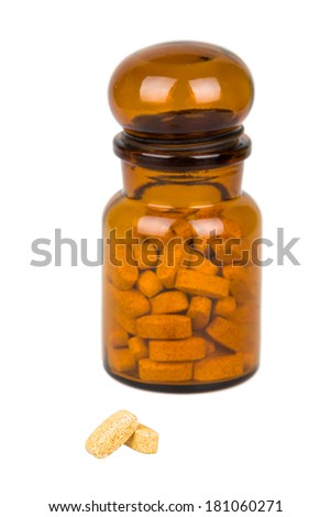 Two pills and apothecary jar isolated on white. Selective DOF. - stock photo