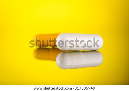 two pills capsule on yellow glass background