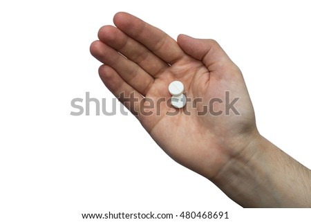 Two pills on the hand of man isolated on white background.