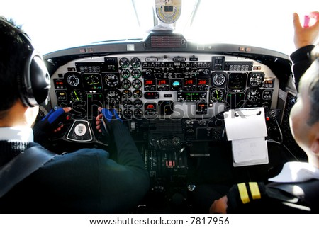 two pilots in cockpit of plane during mountain-flight - stock photo