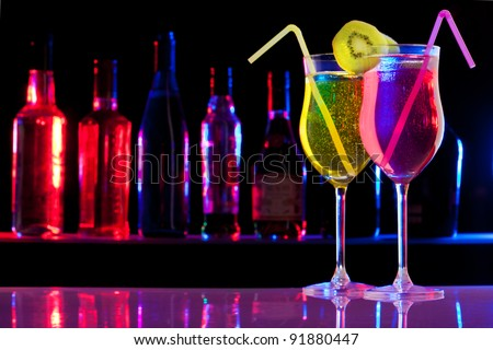 Two pink and yellow cocktails in the glass with straw and kiwi, and bar bottles row on the background - stock photo