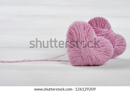 Two pink clews in shape of heart on white wooden background - stock photo