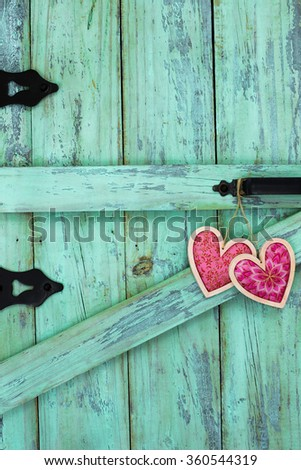 Two pink fabric country hearts hanging on antique mint green rustic wood door - stock photo