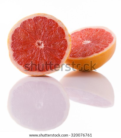 Two pink grapefruit halves with its mirror reflection on a white background isolated close up vertical - stock photo