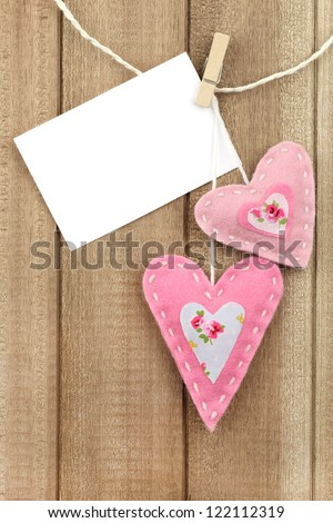 Two pink handmade felt hearts hanging on line with white paper for a Valentine's day love message - stock photo