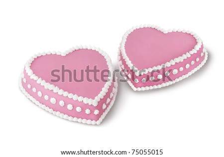 Two pink heart shape marzipan cakes decorated with white whipped cream - stock photo