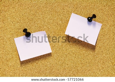 Two pink notes on yellow pinboard - stock photo