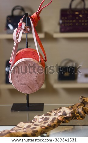 Two pink round small bags hanging on the stand in the shop window. Also on the table is a leopard scarf. - stock photo
