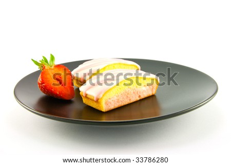 Two pink strawberry sliced cakes with icing on the top with a half strawberry on a black plate on a white background