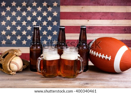 Two pint jars filled with beer, full bottles, football and baseball mitt with vintage wooden USA flag in background.