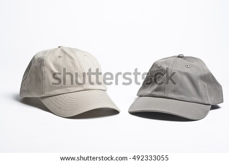 two plain beige baseball caps of different tint
