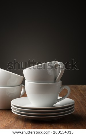Two plain white pottery tea or coffee cups with stacked saucers standing ready on a wooden table to serve a relaxing cup of hot beverage, with vertical copyspace - stock photo