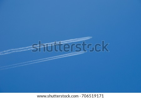 Two planes flying in parallel, leaving behind a white trail.