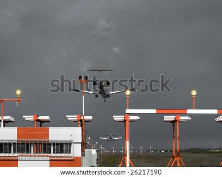 Two planes landing at the same time over a stormy sky - Concept of jammed air traffic. - stock photo