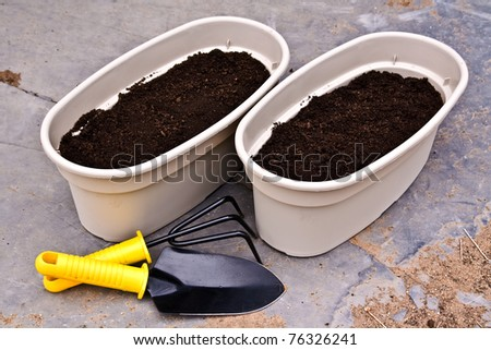 two planters ready for planting flowers and garden tools - stock photo