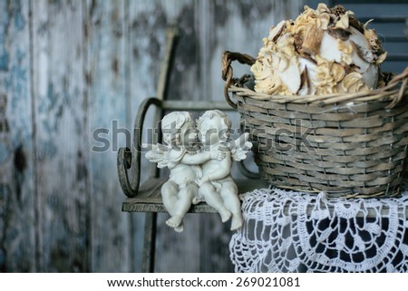 Two plaster angels in the arms sitting on a bench on a vintage background of old wooden planks. - stock photo