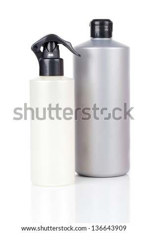 Two plastic bottles of hair care products, with soap or shampoo without label reflected on white background - stock photo