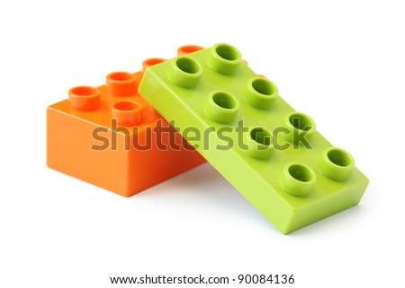 Two plastic toy blocks on white. Focus on near edge of bricks with selective focus. - stock photo