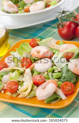 Two plates of Italian shrimp salad with shrimps, tomatoes, artishocke hearts, Romane lettuce leaves, fava beans, and pine nuts. Olive oil.  - stock photo