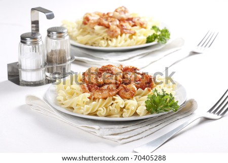 Two plates of pasta with tomato and shrimps