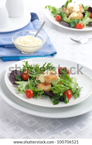Two plates of scallops, cherry tomatoes and spring mix salad with Saffron dressing.