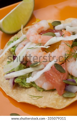 Two plates of shrimp ceviche tostadas with fennel and grapefruit, beer, garnished with mini bell pepper. - stock photo