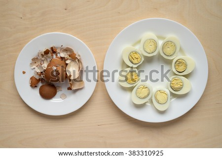 Two plates with eggs and shells on a wooden table - stock photo