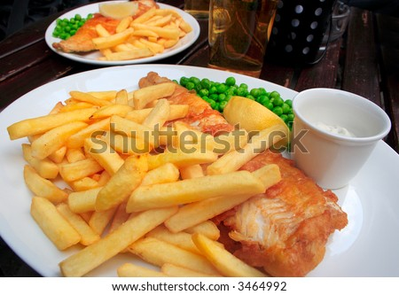 Two plates with fish, chips, peas and sauce on a table. - stock photo