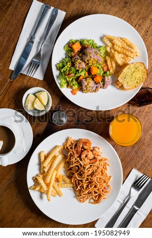 Two plates with the meal on the table, view from above - stock photo