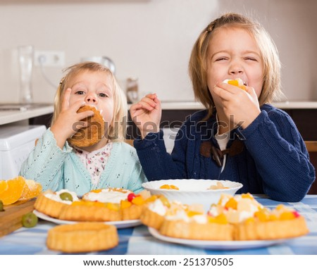 Two playful little girls enjoying pastry with cream in kitchen at home  - stock photo