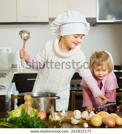 Two playful little sisters learning how to cook at domestic kitchen