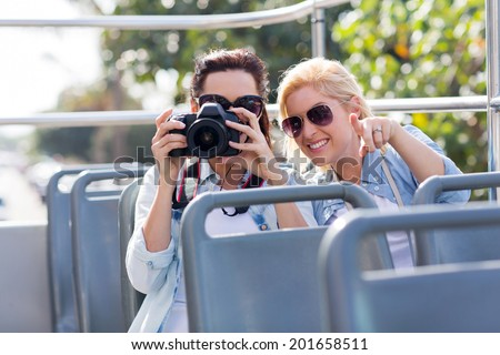two playful tourists taking fun photos from an open top bus while touring the city - stock photo